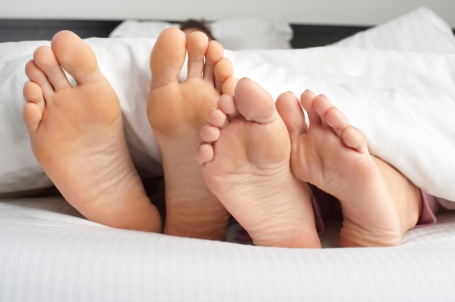 Couple feet poking out at the bottom of the bed